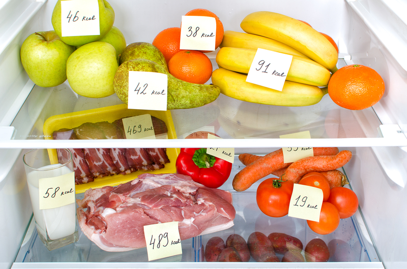 Open fridge full of fruits, vegetables and meat with marked calories.